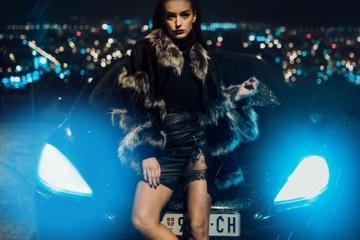 Beautiful escort standing in front of city lights